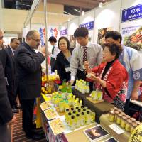 What a spread: Pakistan Ambassador Farukh Amil tastes halal foods at the Japan Halal Expo 2014. | YOSHIAKI MIURA