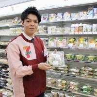 Quick fix: A 7-Eleven shop assistant holds up a boxed, ready prepared salad at a store in the Chiyoda district of Tokyo. | KYODO