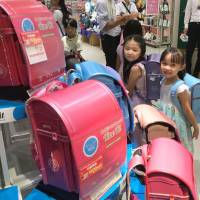 Peer pressure: The obligatory randoseru leather knapsacks Japan's schoolchildren use for carrying books can wind up costing a doting grandparent as much as ¥80,000. | KYODO