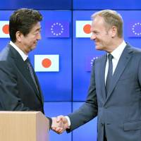 Prime Minister Shinzo Abe and European Council President Donald Tusk shake hands in Brussels on July 6 following a summit that produced a broad agreement on a free trade deal. | KYODO