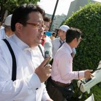 Hate on the mic: Makoto Sakurai, then the leader of the anti-Korean rightist group Zaitokukai, speaks outside Yasukuni Shrine in Tokyo on Aug. 15, 2009. Running as a candidate in Tokyo's gubernatorial election last year, he pledged to pass legislation banning  'harassment of Japanese based on fabricated history,' which he called 'anti-Japanese hate speech. ' | PHOTO- DAMON COULTER — WWW.DAMONCOULTER.COM