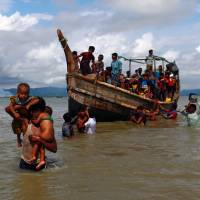 Smoke is seen on Myanmar's side of border as Rohingya refugees leave a boat after crossing the Bangladesh-Myanmar border in Shah Porir Dwip, Bangladesh, on Sept. 11. | REUTERS