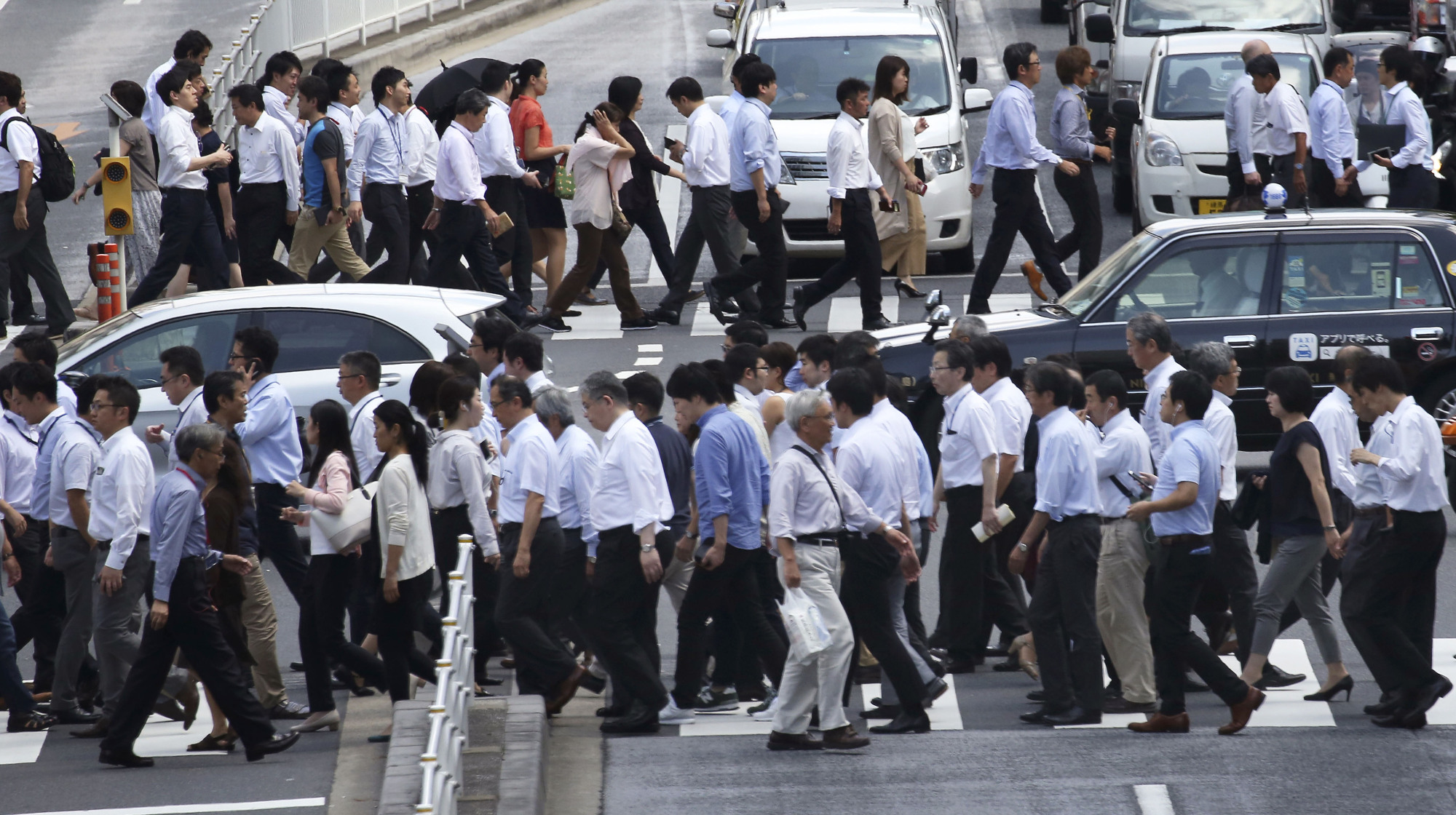 People cross a busy Tokyo street on Sept. 8. In July, the same month wages fell the most in more than two years, Japan's un employment rate hit a 23-year low of 2.8 percent. | AP