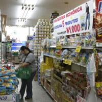 A woman shops at a supermarket for Brazilian residents in Hamamatsu, Shizuoka Prefecture, in this 2008 file photo. Instead of assuming that foreign workers are temporary residents who will eventually depart, Japan's leaders should plan for the reality that many will stay. | AP