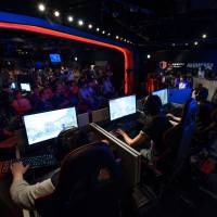 Attendees play Activision Blizzard Inc.'s Overwatch game at the AOC Open e-Sports event in Tokyo on July 1. Japan has been slow to embrace e-sports, but that may change. | BLOOMBERG