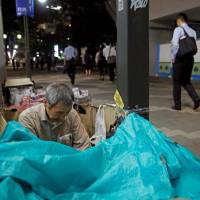 Masayoshi Koiso, 69, prepares to sleep on a street in Tokyo. | REUTERS
