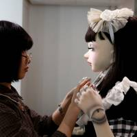 Getting real: Designer Hitomi Komaki puts the final touches on Lulu Hashimoto, a doll suit she created to be worn as fashion. | REUTERS