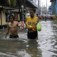 Residents wade though a flooded street in Manila on Tuesday after heavy rains swamped low-lying areas. | AP