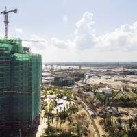 Construction cranes and partially completed buildings stand at Country Garden Holdings Co.'s Forest City development site in the Iskandar economic zone in Malaysia. Country Garden Holdings, a leading Chinese property developer, has reportedly drawn the ire of Beijing for siphoning money out of China's  domestic economy. | BLOOMBERG