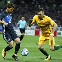 Takuma Asano vies for the ball with Australia's Matthew Spiranovicin their World Cup qualifier at Saitama Stadium on Thursday. Japan won 2-0 to clinch qualification for the 2018 World Cup in Russia. | AP