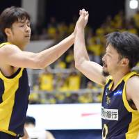 Brex guard Yuta Tabuse (right) high-fives teammate Kosuke Takeuchi after making a shot during the third quarter on Friday in Utsunomiya, Togichi, Prefecture. The Brex won 78-64 in the B. League season opener for both teams. | KYODO