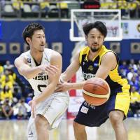 The SeaHorses' Ryoma Hashimoto (left) makes a pass while being defended by Brex guard Yuta Tabuse during the first quarter on Friday. | KYODO
