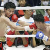 Shun Kubo (left) takes on Daniel Roman of the United States during their WBA super bantamweight title fight in Kyoto on Sunday. | KYODO