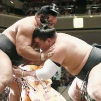 Harumafuji (right) grapples with Shohozan on Saturday at the Autumn Grand Sumo Tournament. | KYODO