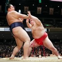Onosho (right) forces Asanoyama out of the raised ring on Saturday, the 14th day of the Autumn Grand Sumo Tournament, at Ryogoku Kokugikan. | KYODO