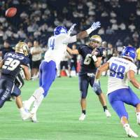 IBM defensive end James Brooks pressures Obic quarterback Shun Sugawara early in the third quarter on Tuesday night, helping defensive back Tatsuma Kobayashi make an interception. Kobayashi returned the interception 98 yards for a touchdown as the BigBlue defeated the Seagulls 38-36. | KAZ NAGATSUKA