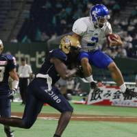 IBM reserve quarterback Yuki Masamoto evades a tackle by Obic defensive end Kevin Jackson and jumps into the end zone for a touchdown in the third quarter. | KAZ NAGATSUKA