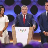 IOC president Thomas Bach speaks between Paris Mayor Anne Hidalgo and Los Angeles Mayor Eric Garcetti after Paris 2024 and Los Angeles 2028 were ratified as host cities for the Olympics during the IOC session in Lima on Wednesday. | REUTERS
