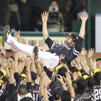 Dennis Sarfate is given a traditional doage (victory toss) after the Hawks beat the Lions to clinch the Pacific League pennant on Saturday. | KYODO