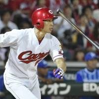 The Carp's Tomohiro Abe hits a two-run double against the BayStars on Wednesday night in Yokohama. | KYODO