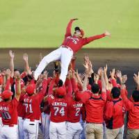 The Carp give manager Koichi Ogata a traditional doage (victory toss) after beating the Tigers to clinch the Central League pennant on Monday in Nishinomiya, Hyogo Prefecture. | KYODO
