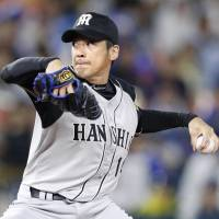 Tigers southpaw Atsushi Nomi pitches against the BayStars on Thursday at Yokohama Stadium. Hanshin defeated Yokohama 11-2, with Nomi tossing a complete game. | KYODO