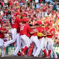The Carp rush to the mound in celebration after clinching their second straight Central League pennant with a 3-2 win over the Tigers on Monday in Nishinomiya, Hyogo Prefecture. | KYODO