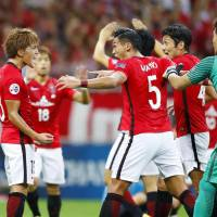 Urawa's Toshiyuki Takagi (left) celebrates with his teammates after scoring against Kawasaki in the second leg of their Asian Champions League quarterfinal on Wednesday. | KYODO