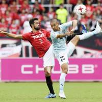 Urawa Reds' Mauricio (left) and Jubilo Iwata's Kengo Kawamata compete for the ball during their 1-1 draw in the J. League on Sunday. | KYODO