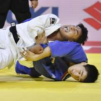 Soichi Hashimoto (left) battles a South Korean judoka during the mixed team event at the world championships on Sunday in Budapest. | KYODO