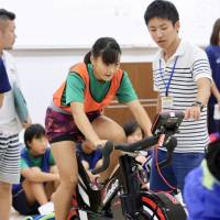 An applicant for the Japan Rising Star Project rides a training bike during an Aug. 26 event at Nippon Sport Science University. | KAZ NAGATSUKA