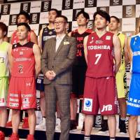 B. League chairman Masaaki Okawa (center) and players from each of the top-division clubs pose for a photo at the league's tip-off conference at a Tokyo hotel on Monday. | KAZ NAGATSUKA