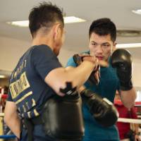 Ryota Murata punches his trainer's mitt during a training session on Friday in Tokyo ahead of his rematch with Hassan N'Dam for the WBA middleweight title. | KAZ NAGATSUKA