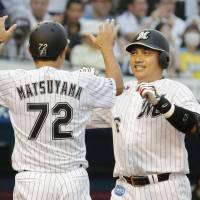 Chiba Lotte's Tadahito Iguchi (right) celebrates his ninth-inning, two-run home run with coach Hideaki Matsuyama during the Marines' 4-3 win over the Fighters on Sunday. | KYODO