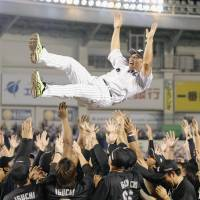 Chiba Lotte players throw Tadahito Iguchi in the air after Sunday's game against the Fighters at Zozo Marine Stadium. | KYODO