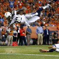 Los Angeles Chargers running back Melvin Gordon dives over Denver's Justin Simmons for a touchdown in the first half on Monday night. | AP