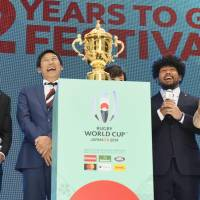 Participants at an event to mark two years to go until the 2019 Rugby World Cup, including Sports Agency commissioner Daichi Suzuki (second left) and Japan national team player Shota Horie (second right) share a joke in Tokyo on Wednesday. | KYODO