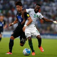 Japan's Hiroki Sakai (left) vies with Saudi Arabia's Fahad Al Muwallad during their World Cup qualifier in Jeddah on Tuesday. | REUTERS