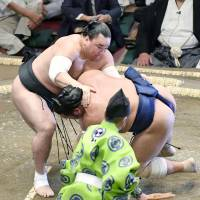 Yokozuna Harumafuji takes down Tochiozan on the opening day of the Autumn Grand Sumo Tournament on Sunday at Tokyo's Ryogoku Kokugikan. | KYODO