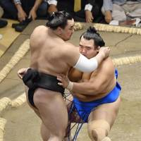 Maegashira Kotoshogiku (right) forces yokozuna Harumafuji out of the raised ring on Tuesday at Ryogoku Kokugikan. | KYODO