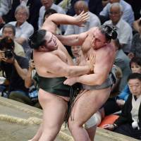 Chiyotairyu (left) outmuscles Tochinoshin in an Autumn Grand Sumo Tournament match on Tuesday at Ryogoku Kokugikan. | KYODO