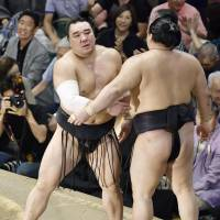 Harumafuji (left) reacts after beating Goeido in a playoff to win the Autumn Grand Sumo Tournament on Sunday. | KYODO