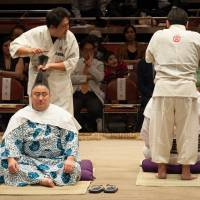 Rikishi participate in a topknot tying demonstration during the Ozumo Beyond 2020 Basho last year. | JOHN GUNNING