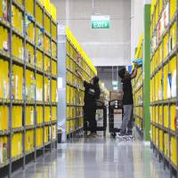 Employees pack orders at Amazon.com Inc.'s Amazon Prime Now fulfillment center in Singapore, in July. | BLOOMBERG