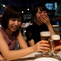 Female customers toast with beer at a Tokyo restaurant on Aug. 29. | REUTERS