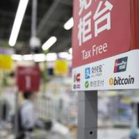The bitcoin logo is seen at the information desk of the Bic Camera Akiba electronics store run by Bic Camera Inc. in Tokyo's Akihabara district in June. More Chinese bitcoin operators are looking to run businesses in Japan because China's authorities have tightened regulations. | BLOOMBERG
