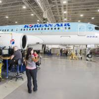 Bombardier employees work on C eries 300 jets at the company's plant Thursday in Mirabel, Quebec. | RYAN REMIORZ / THE CANADIAN PRESS / VIA AP