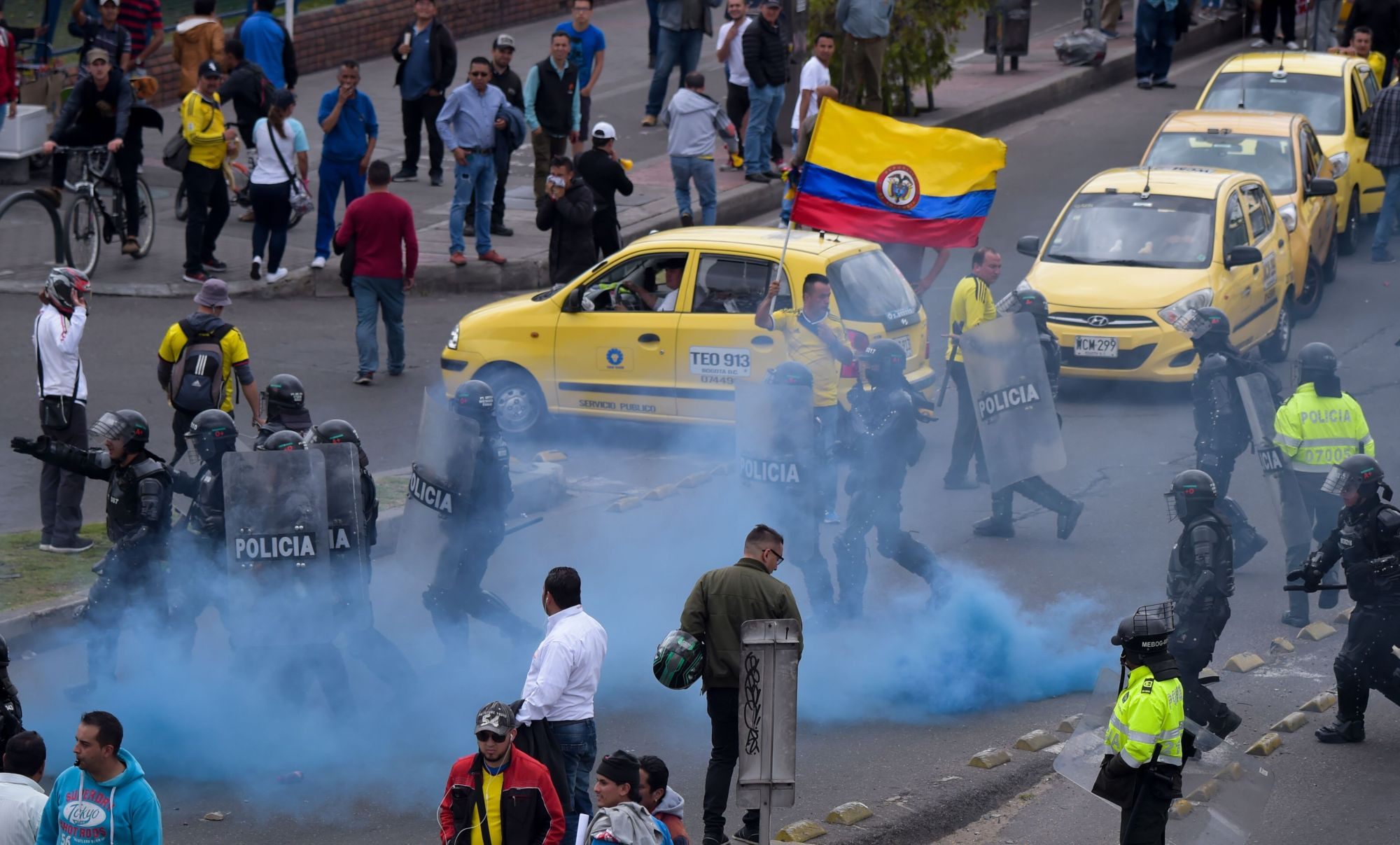 Police officers try to disperse a protest staged by taxi drivers over the private hire company Uber in Bogota Monday. | AFP-JIJI
