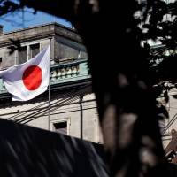 The Japanese flag flutters atop the Bank of Japan. | REUTERS