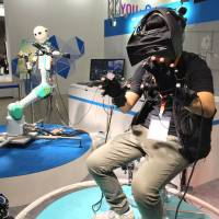 The Telesar V robot copies the movement of a person through wearable control devices Tuesday in the KDDI Corp. booth at the Combined Exhibition of Advanced Technologies (CEATEC) at Makuhari Messe in the city of Chiba. | SHUSUKE MURAI